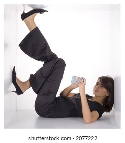 businesswoman with palmtop/mobile phone in the cramped white cube