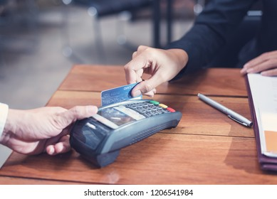 Businesswoman paying by credit card with a credit card reader machine in a restaurant