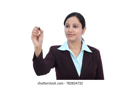 Businesswoman with pen writing on virtual screen