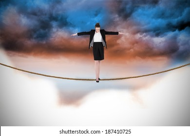 Businesswoman performing a balancing act against blue orange cloudy sky background