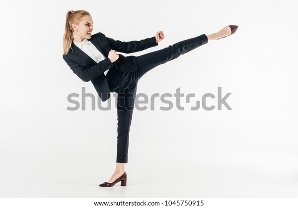 businesswoman performing karate kick in suit and high heels isolated on white