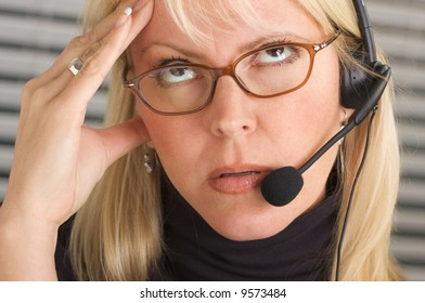 Businesswoman with phone headset show signs of having a headache.