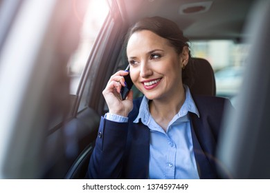 Businesswoman with phone on the back seat of a car