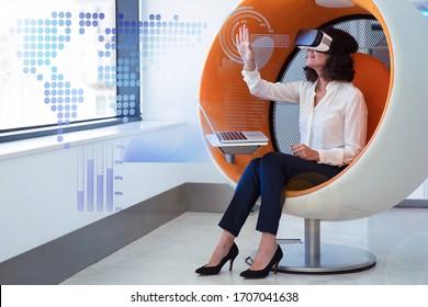 Geschäftsfrau spielt VR-Spiel und virtuelle statistische Grafiken. Frauen in Bürokleidung und Brille mit virtueller Realität sitzen im interaktiven Stuhl mit Laptop und berührender Luft. VR-Wildkonzept