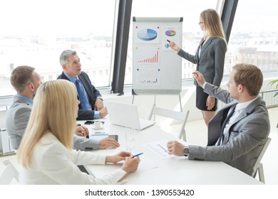 Businesswoman pointing at a chart on a whiteboard during business meeting