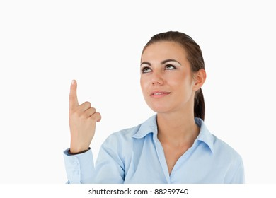 Businesswoman pointing with her finger upwards against a white background