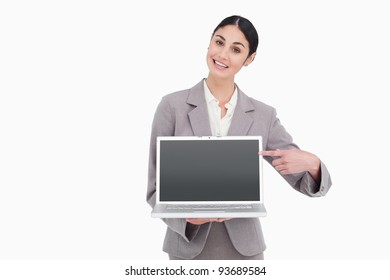 Businesswoman pointing at screen of her laptop against a white background