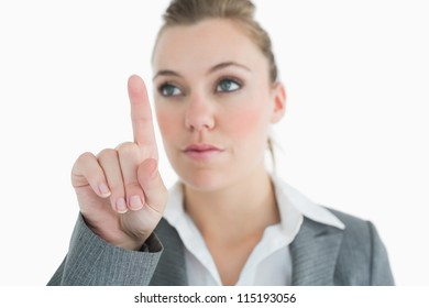 Businesswoman pointing at something above her while concentrating