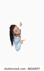 Businesswoman pointing while looking around the corner against a white background