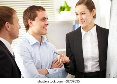 A businesswoman pointing at a whiteboard before her colleagues