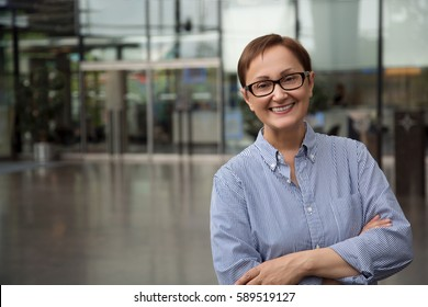 Businesswoman. Portrait of middle aged woman in the office space. Headshot of female 40 50 years old wearing glasses and shirt looking at camera