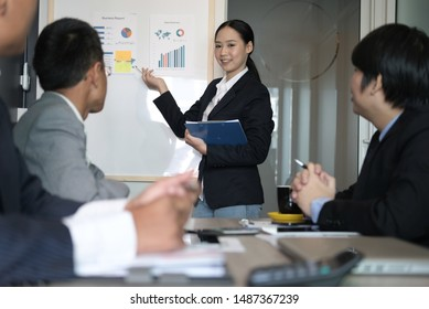 businesswoman present financial plan report to co worker team. woman leader  discuss sales data with investor colleagues. finance investment business meeting at office