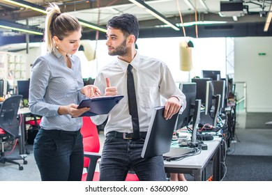 Businesswoman presenting business plan to her male colleague. He is looking at her and showing thumb up.