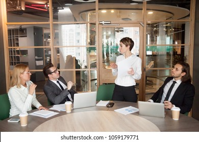 Businesswoman presenting document or speaking about new business project results at group meeting, female manager holding contract making sales offer to investors or clients explaining deal benefits
