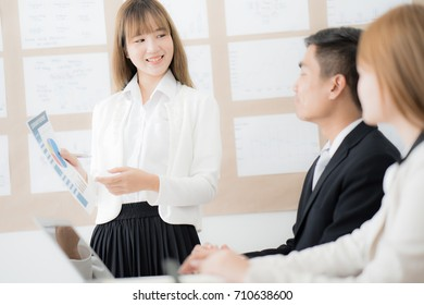 Businesswoman presenting financial to partners in office. Asian people