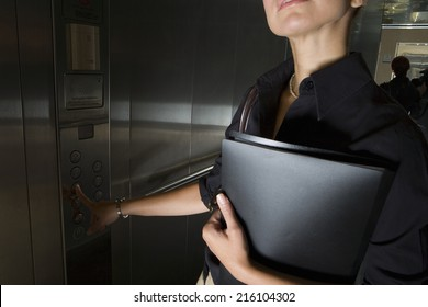Businesswoman pressing button in elevator, mid section