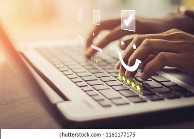 Geschäftsfrau drücke Gesichtseemoticon auf dem Keyboard-Laptop / Kundenservice-Auswertungskonzept.