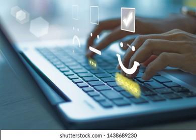 Femme d'affaires pressant l'émoticon du visage sur l'ordinateur portable du clavier. Ton bleu