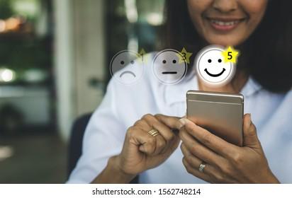 Geschäftsfrau drückt Gesichtsgefühle auf einem virtuellen Touchscreen am Smartphone. Kundenservice-Auswertungskonzept.