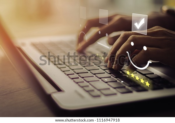 Businesswoman pressing smiley on keyboard laptop .Customer service evaluation concept.