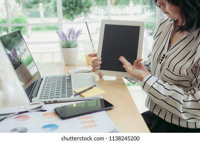 Businesswoman professionals having a presenting in office lobby using digital tablet. Business partners using touchscreen computer for project discussion.