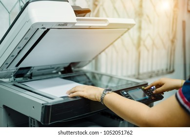 businesswoman put documents on printer for scanning and copying in office