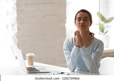 Businesswoman put hands together in prayer, meditating, relaxing sitting at workplace with closed eyes, enjoying meditation, reduce stress, keep calm and positive thinking, relaxing in office