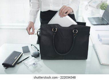 Businesswoman putting essential things into her handbag, starting with tablet computer