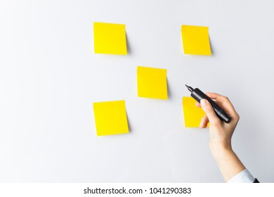 Businesswoman putting her ideas in sticky-note planning on business strategy
