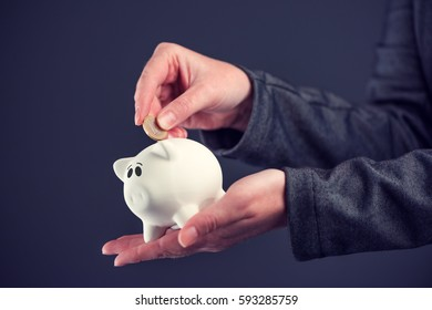 Businesswoman putting one euro coin in piggy bank, money savings and home budget concept