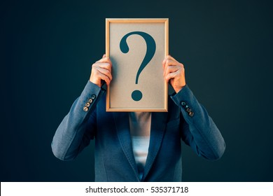 Businesswoman with question mark looking for answers, questioning and wondering about uncertain future in corporate business