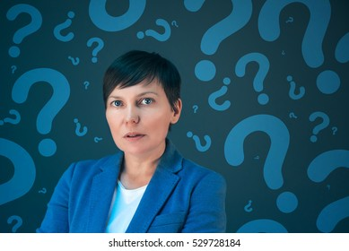 Businesswoman with question marks looking for answers, questioning and wondering about uncertain future in corporate business