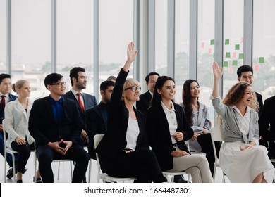 Businesswoman raising hand during meeting in office. young people sitting on conference together while one man raising his hand