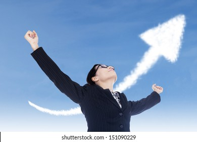 Businesswoman raising her arms with up arrow sign as background