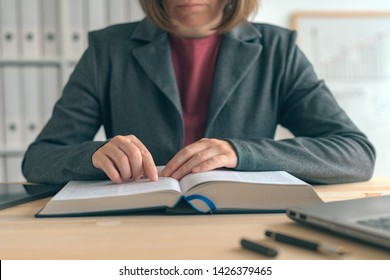 Businesswoman reading book at office desk, searching for the business realted information