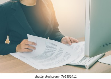 Businesswoman reading and checking terms and conditions document on her working space, business concept