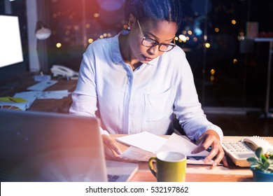 Businesswoman reading document at desk in office