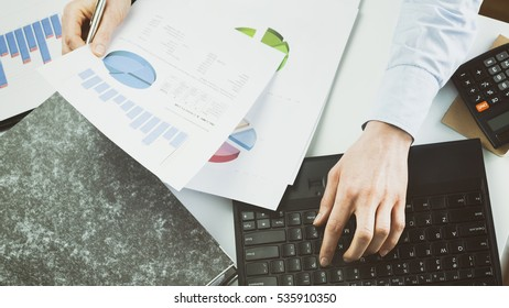 Businesswoman reading or inspecting financial documents on her desk. Top view, shallow DOF, focus on the computer and the paperwork.