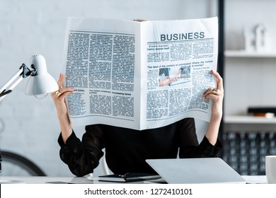 businesswoman reading newspaper and hiding face