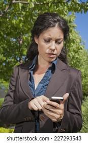 businesswoman reading smartphone in exterior background