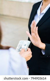 Businesswoman refusing money offered by a woman - anti bribery and corruption concepts