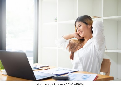 Businesswoman relaxing at comfortable in office hands behind head, happy woman resting in office satisfied after work.