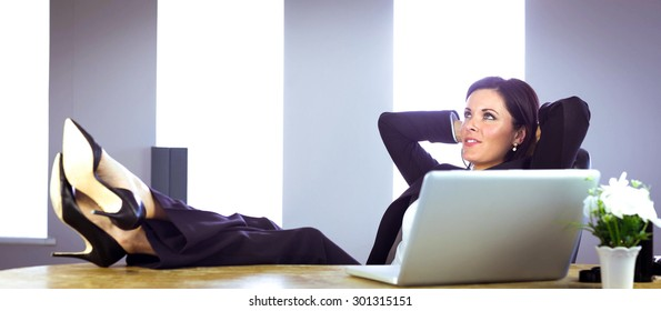 Businesswoman relaxing at her desk in her office