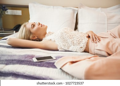 Businesswoman relaxing in hotel room, holding hands behind head and smiling while lying in bed, copy space