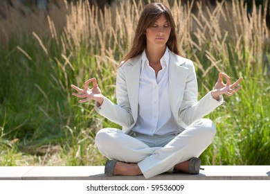 businesswoman relaxing in a zen like position outdoors