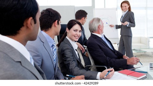 Businesswoman reporting sales figures to her team in the office