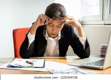 Businesswoman resting hands on head with eyes close at work desk in office.