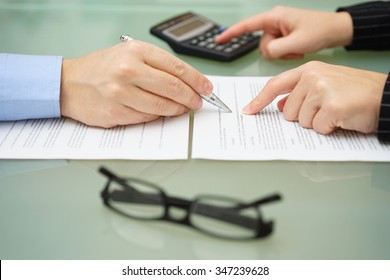 businesswoman is reviewing document with tax consultant and making calculations to optimize report