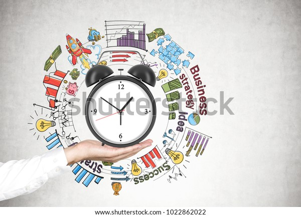 Businesswoman s hand in a white shirt with an alarm clock near a concrete wall with a time management sketch on it.