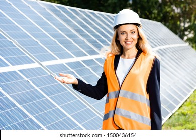 businesswoman in safety vest and hardhat smiling and looking at camera